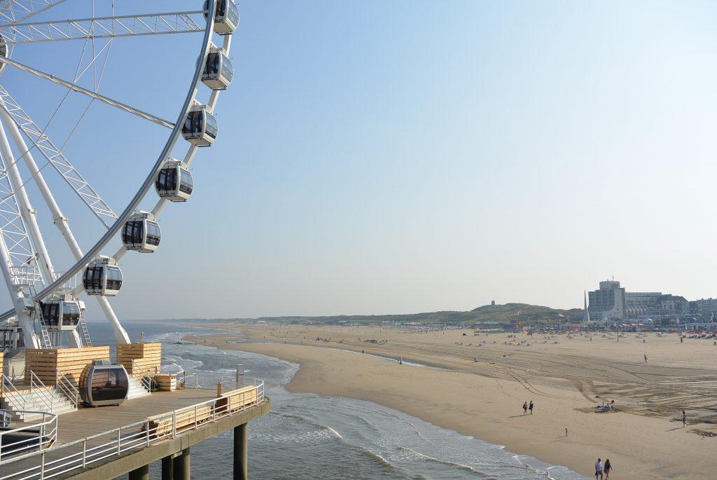 Het reuzenrad en strand vanaf de pier